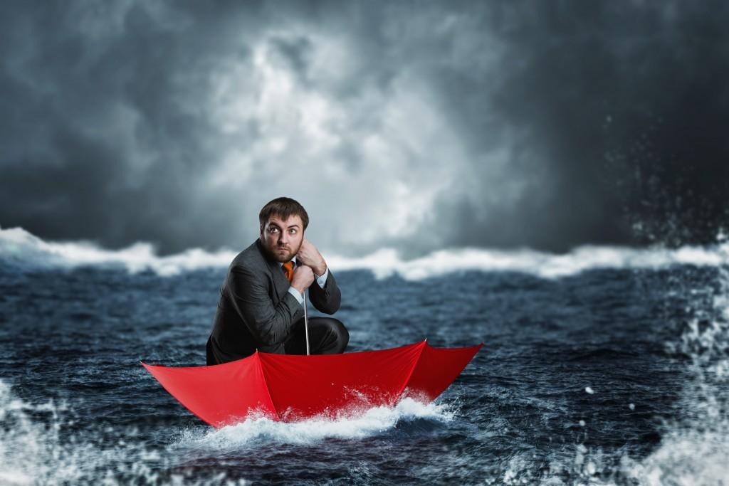 Scared businessman in the umbrella sails in the sea in the night